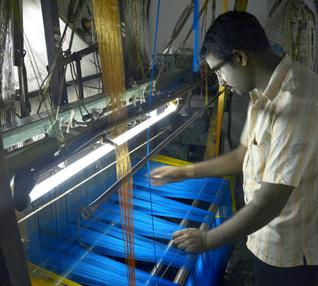 Venkatesh, a weaver, works on a powerloom unit near Gottigere in Bangalore (Image Courtesy: The Hindu)