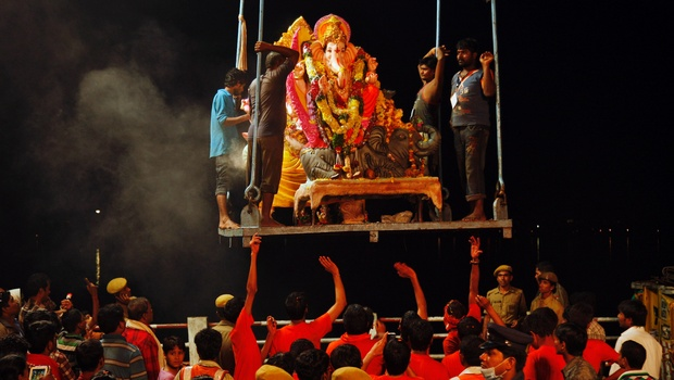 Devotees lift an idol of Lord Ganesha before immersing it in the Hussain Sagar Lake during Ganesh Chaturthi in Hyderabad. (Image: Newindianexpress.com)