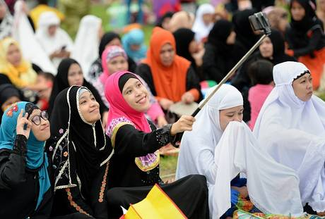 Young Philippines women in their traditional attires take a 'selfie' prior to Eid prayers in Manila. (Image: Independent.co.uk)