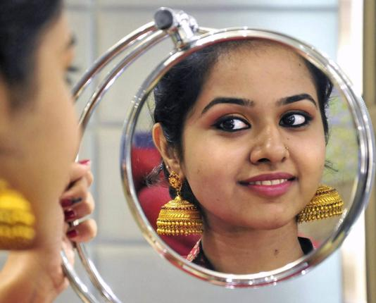 A young girl tries on Jhumkas. (Image: Thehindu.com)