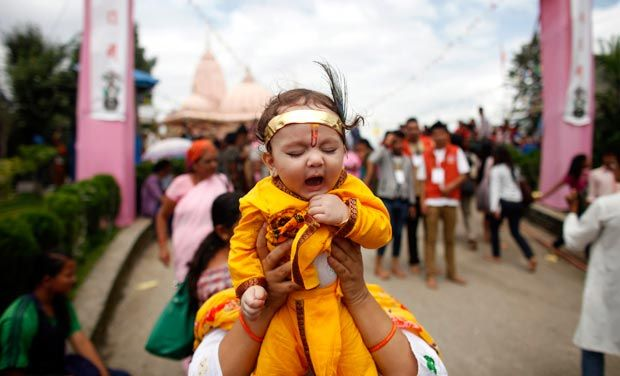 This 2013 picture shows a Nepalese woman carrying her child dressed as Krishna during the Janmashtami festival at a Lord Krishna temple in Lalitpur, Nepal. (Image: Archives.deccanchronicle.com)